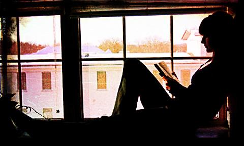Chica leyendo en la ventana.